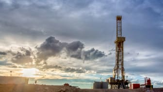 Dusk or Dawn image of a fracking drilling rig under a beautiful cloudscape and dreamy golden light
