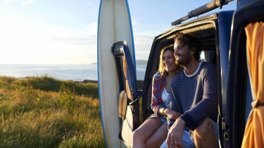 A couple sits in the boot of their van while looking out at the beach