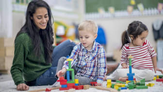 A preschool boy and girl are indoors with their teacher. They are sitting on the floor and playing with colorful blocks together.