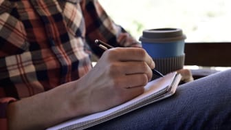 closeup of a young caucasian man wearing jeans and a plaid shirt writing with a pen in a notebook in the porch of a house or a ranch