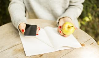 young girl with cell phone, diary and green apple