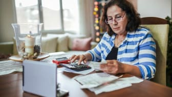 A woman uses a calculator, a laptop and paperwork to calculate benefits