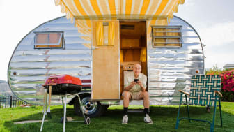 Retired man sitting in the door of a retro RV
