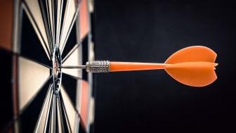 A dart going into a dartboard.