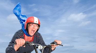 A woman happily rides a bike with her scarf blowing in the wind.