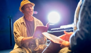Senior actor on stage reading a script.