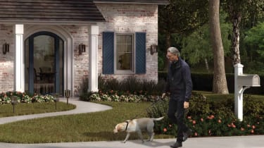 A senior man walking a dog outside a suburban home