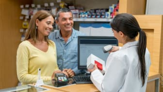 Pharmacist serving happy customers paying at the drugstore