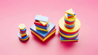 Still life of three colorful stacks of toy blocks on pink background