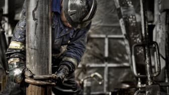 Oil Rig Worker wearing his safety gear working on the muddy drill floor