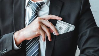picture of a man putting money in his suit pocket
