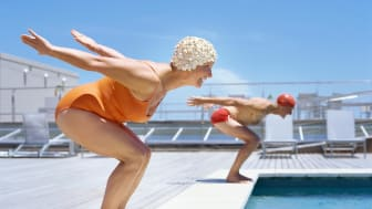 Two happy women getting set to dive into a pool