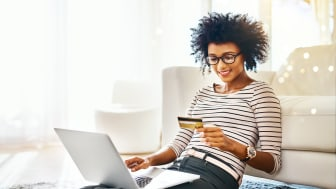 Shot of a cheerful young woman doing online shopping on her laptop while being seated on the floor at home