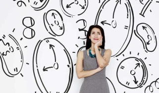A woman surrounded by drawings of clocks