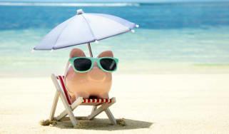 piggy bank sitting in umbrella chair at the beach