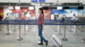 Asian tourist with luggage ,wearing mask to prevent during travel time at the airport terminal for protect from the new Coronavirus 2019 infection outbreak situation