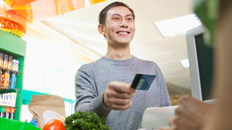 A smiling man hands a gift card to a cashier