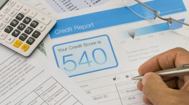 Credit report form on a desk with other paperwork. There are also a pen, glasses and a calculator on the desk. Hand is holding pen