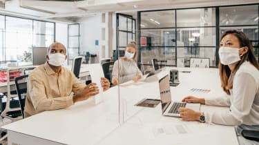 Several mask-wearing office workers sitting at a desk, separated by glass partitions