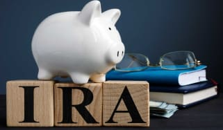 picture of piggy bank sitting on blocks spelling out I-R-A