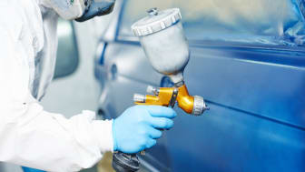 automobile repairman painter hand in protective glove with airbrush pulverizer painting car body in paint chamber (automobile repairman painter hand in protective glove with airbrush pulveriz