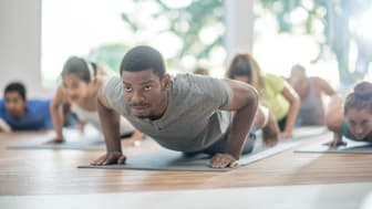 A man doing yoga looks around during class.