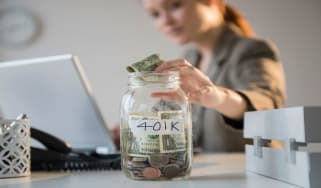 picture of woman putting money in a jar labeled 401K