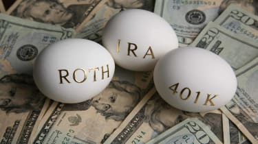 """3 eggs with """"Rpth,"""" """"IRA,"""" and """"401K"""" written on them sitting an a pile of U.S. dollars"""