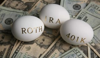 "3 eggs with ""Rpth,"" ""IRA,"" and ""401K"" written on them sitting an a pile of U.S. dollars"