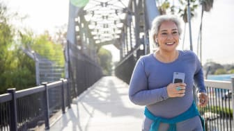 Smiling senior woman running on a trail while holding her mobile phone