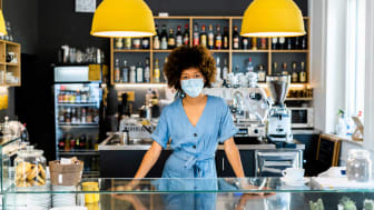 A COVID-masked employee stands behind the counter of a coffee shop