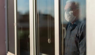 Senior man wearing COVID mask sadly stares out a window