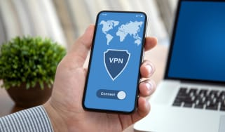 male hand holding phone with app vpn over laptop
