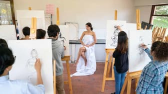 Group of people painting a live model in an art class using a canvas and an easel - education concepts