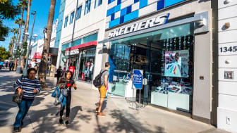 People stand outside a Skechers storefront
