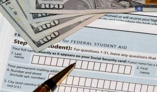 Student aid form with hundred dollar bills and pen resting on it