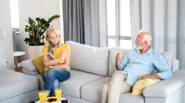 Senior couple discussing divorce while sitting in their living room