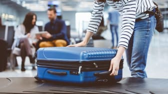 Young woman passenger collecting her luggage from conveyor belt. Female traveler picking up suitcase from baggage claim line in airport terminal.