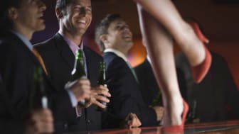 picture of men at a bar watching a woman dance on the bar