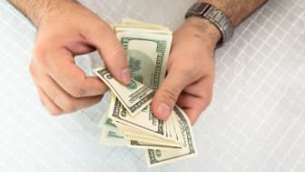 Close-up of a man hands counting dollar notes
