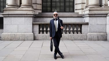 A white-haired man in a suit with a briefcase.