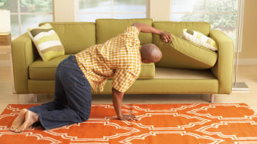 picture of man looking for something under a couch cushion