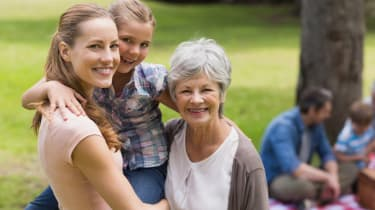 Grandmother, mother and daughter with family in background at park