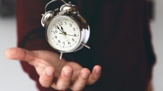 A hand holding an old-fashioned alarm clock