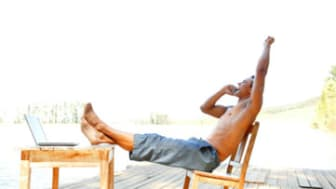 Shirtless man on cell phone on dock