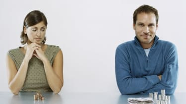 Man and Woman Sit Next to each Other With a Pile of Money in Front of Them, Woman Looking Jealous at Man's Pile