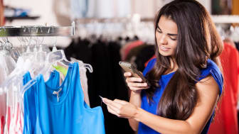Pretty Latin woman taking a snapshot of a price tag in a clothing store