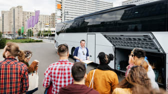 A group representative standing in front of a bus, taking a headcount of his fellow travellers before the journey.