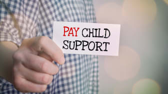 "picture of man holding note saying ""pay child support"""