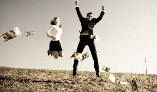 A couple jumps up and down in a field where cash is raining down